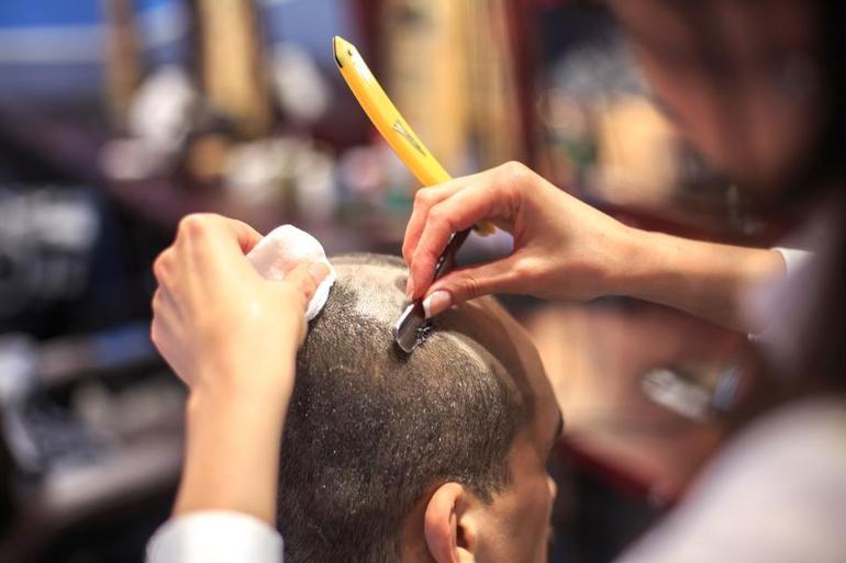 Парикмахер станком сбривает волосы с головы