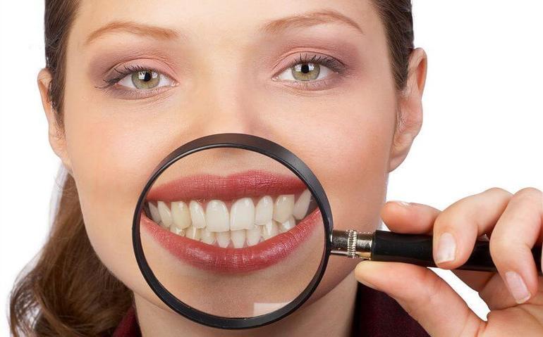 Человек рассматривает собственные зубы,