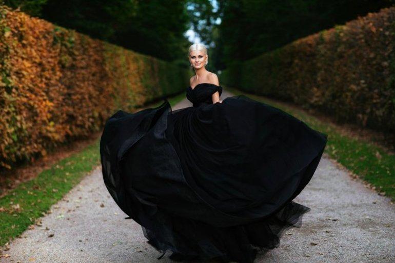 В темное платье облачена подруга девушки,